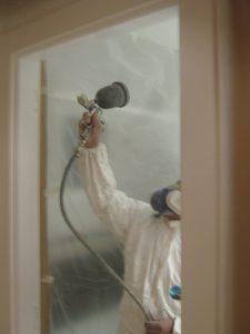 Pintores en Bergara Pintor especialista aplicando laca en puerta en San Sebastián.